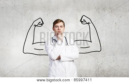 Young male doctor with drawn strong hands behind his back