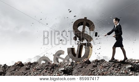 Young businesswoman crashing with hammer stone dollar symbol