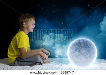 Cute boy sitting in bed and dreaming about moon
