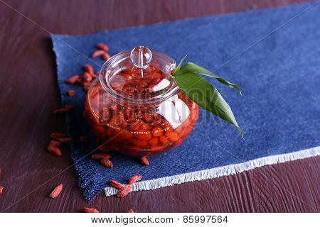 Jar of goji berry jam on napkin on wooden background