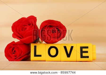 Decorative letters forming word LOVE with flowers on wooden background