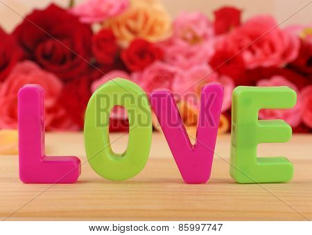 Decorative letters forming word LOVE with flowers on bright background