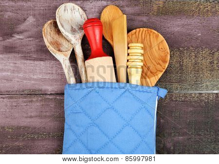 Different kitchen utensils in potholder on wooden background