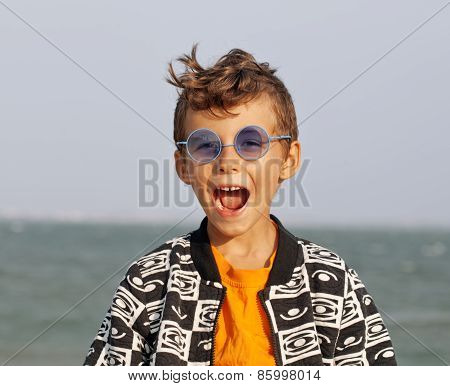 cute little boy at seacoast in fashion clothers and blue glasses