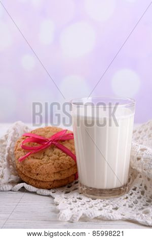 Tasty cookies and glass of milk on color wooden table, on bright background