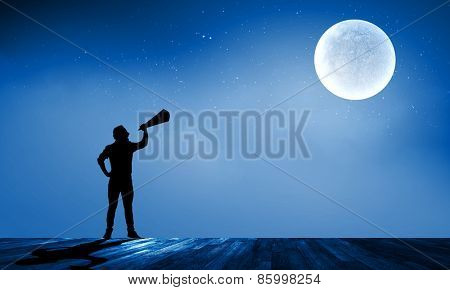 Silhouette of man at night screaming in megaphone