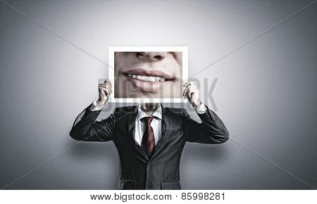 Businessman hiding head behind photo with huge mouth