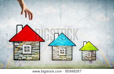 Close up of human hand taking model of house