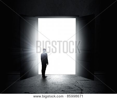 Rear view of businessman standing in light of opened door
