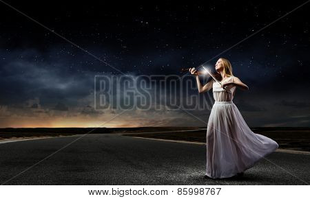 Young woman in white dress playing violin