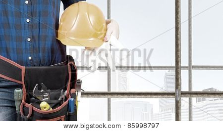 Close up of woman builder with hardhat in hands