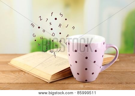 Open book with flying letters on table on bright background