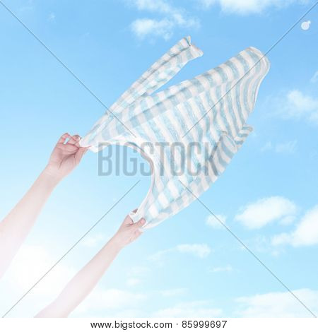 Hands holding flying shirt on sky background