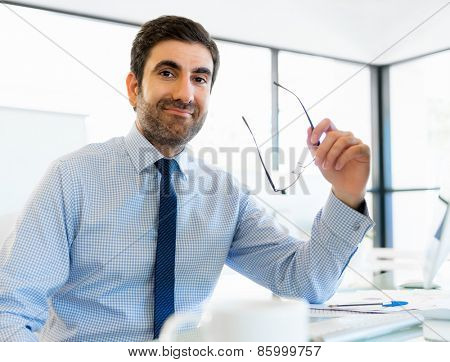 Young businessman in office sitting and smiling
