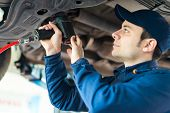 picture of auto repair shop  - Mechanic changing car wheel in auto repair shop - JPG