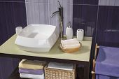 pic of sink  - detail of a modern bathroom with sink and accessories bathroom cabinet and purple bathroom tiles - JPG
