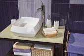 foto of bathroom sink  - detail of a modern bathroom with sink and accessories bathroom cabinet and purple bathroom tiles - JPG