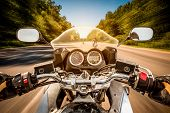 pic of driving  - Biker driving a motorcycle rides along the asphalt road - JPG