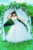 stock photo of wedding arch  - Beautiful elegant asian bride stands under the wedding arch - JPG