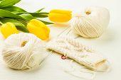 foto of knitting  - roll of white soft knitting yarn knitting mittens and yellow tulips on lighten background - JPG
