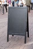 pic of pedestrians  - blank blackboard advertising street sign with unrecognizable pedestrians in the background - JPG