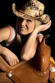 stock photo of cowgirls  - A cowgirl with a big smile leaning on her saddle - JPG