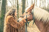 Image of woman stroking horse.