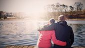 picture of pier a lake  - Retro filtered photo of a couple sitting on wooden pier by lake - JPG