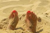 stock photo of painted toenails  - Woman feet on the sand with manicure - JPG