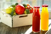 stock photo of crate  - Bottles of juice with fruits and vegetables  in crate on windowsill - JPG