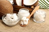 stock photo of sackcloth  - Coconut with jars of coconut oil and  cosmetic cream on sackcloth background - JPG
