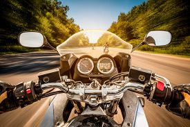 pic of biker  - Biker driving a motorcycle rides along the asphalt road - JPG