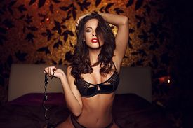 picture of handcuff  - Sexy woman kneeling and holding handcuffs on bed bdsm - JPG