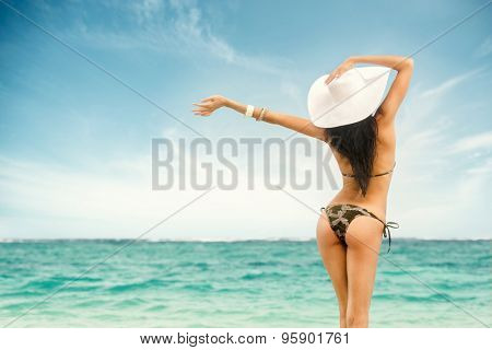 Woman in swimsuit and hat at sea, rear view