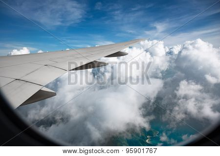 View from a jet plane window high on the blue sky with clouds