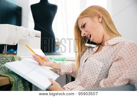 Fashion female designer talking on the phone with disgust emotion and looking at her notes