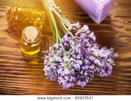 Lavender flowers with essential oil on wooden background. Wellness still-life.