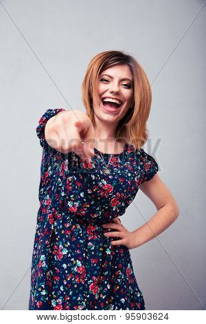 Laughing woman pointing at camera over gray background