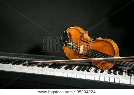 Piano keyboards with old violin on dark background.