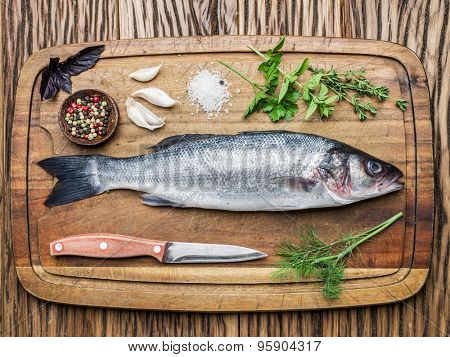Fish - seabass on a wooden board with spices and herbs.