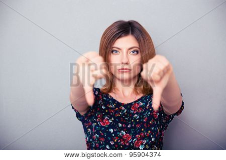 Portrait of a woman showing thumbs down over gray background. Looking at camera