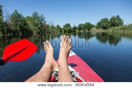 Man's legs over canoe. Resting time.