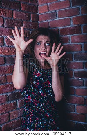 Frightened young woman standing in corner of brick wall