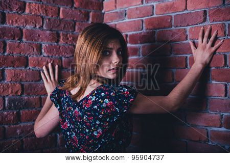 Scared young woman standing in corner of brick wall and looking at camera