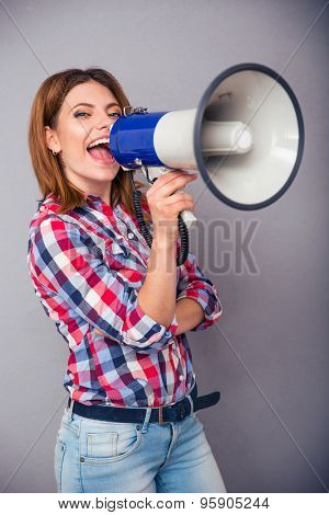 Happy casual woman shouting in megaphone over gray background and looking at camera