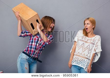 Two women quarrel over gray background