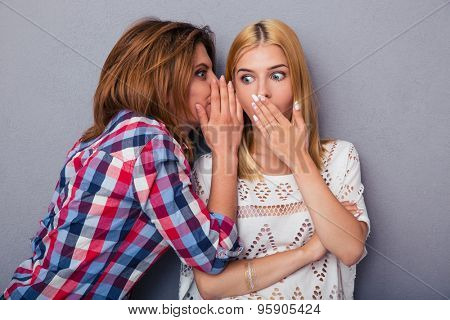 Woman telling gossip to her girlfriend over gray background