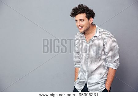 Portrait of a surprised casual man standing over gray background. Looking away