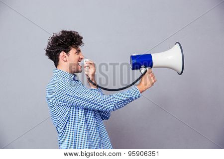 Casual man shouting on megaphone over gray background