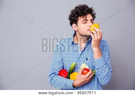 Young man holding smelling vegetables over gray background